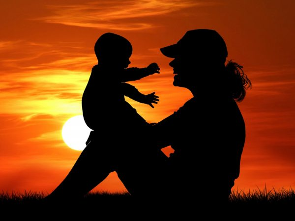 silhouette of mother holding child on her knee with a sunset in the background